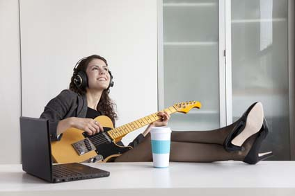 Businesswoman playing guitar at desk
