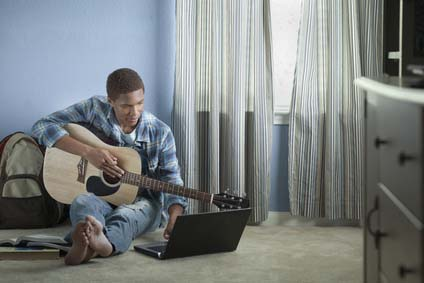 boy holding guitar and using internet